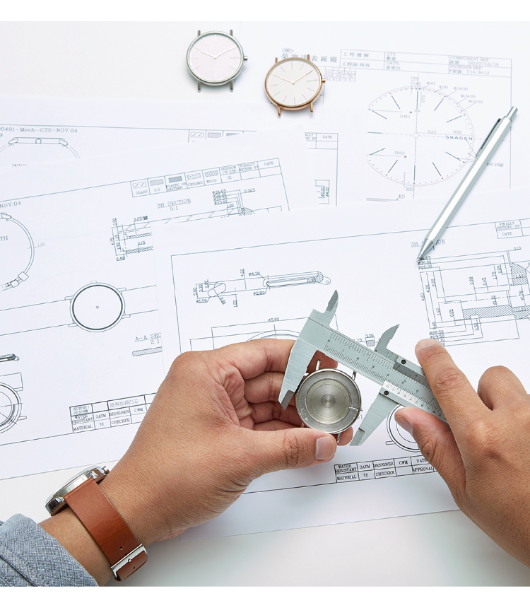 a watch designer measuring a watch case over a table of design schematics and tools