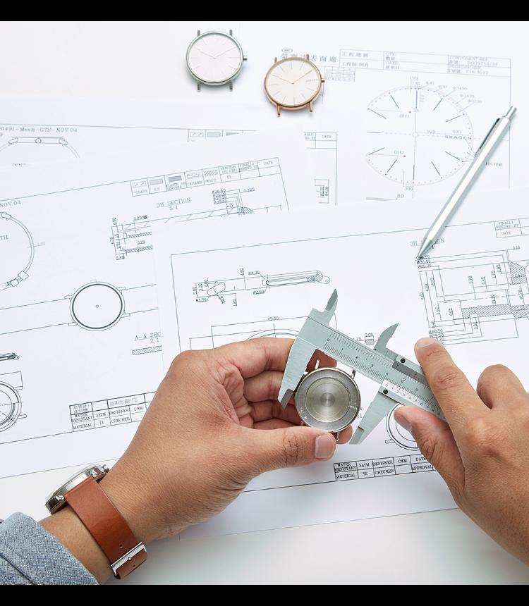 デザイン図とツール表の上で時計ケースを計測する時計デザイナー
