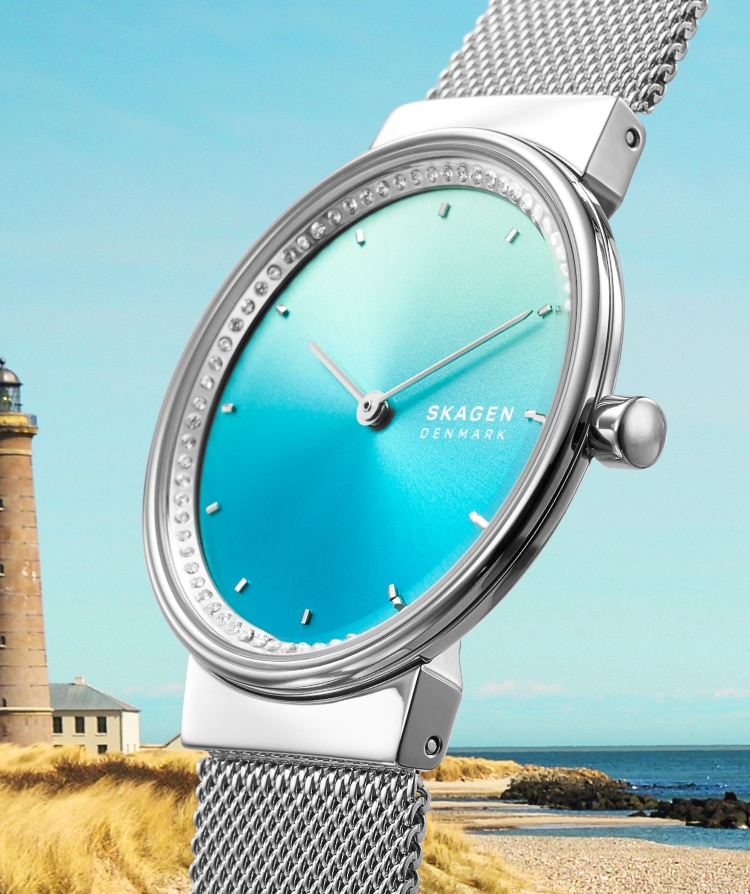 a skagen solar watch with a blue face with a lighthouse in the background
