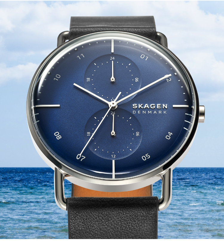A Skagen watch with a blue face and black strap and an image of the ocean in the background