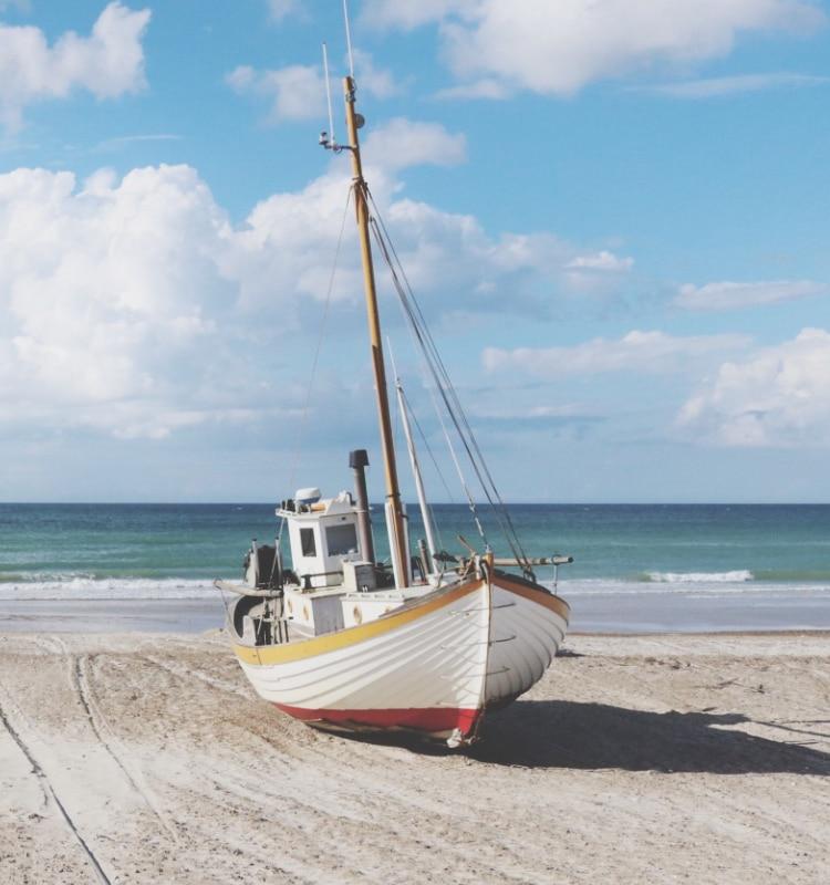 Eine Szene mit bunten Booten an einem Strand mit dem Meer im Hintergrund