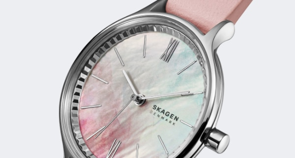 Silver tone case with a pastel mother-of-pearl dial and pink leather strap.