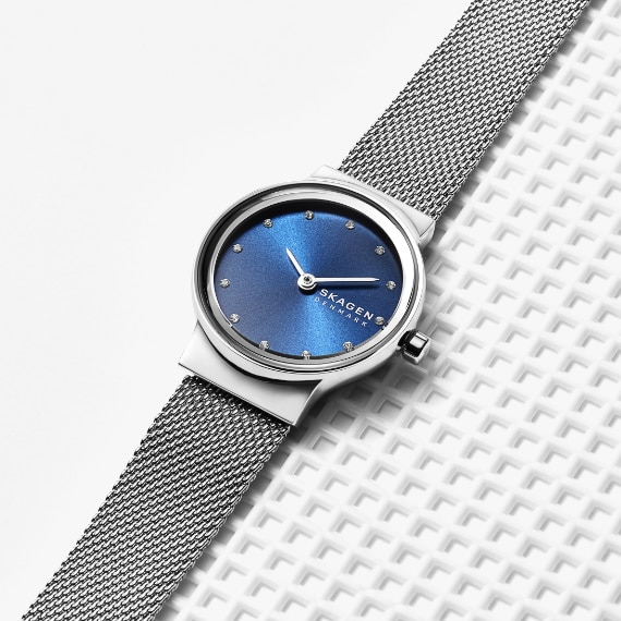 a stainless steel skagen watch with a blue face and steel mesh strap